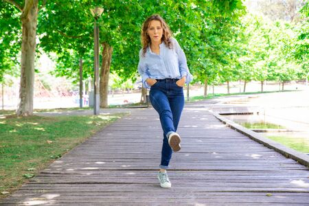 Carefree young woman in casual outfit walking straight leg raise. Positive girl with wavy hair strolling in park. Playful girl concept