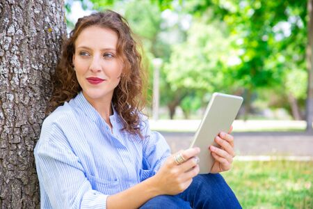 Content pretty girl with curly hair sitting by tree in park. Inspired curly-haired lady using digital tablet outdoors. Online communication concept Stock Photo