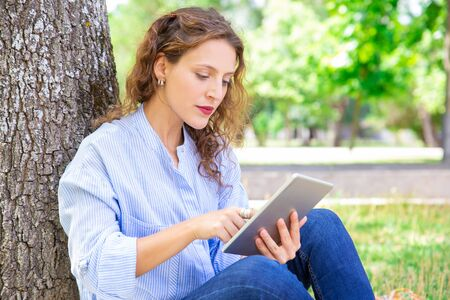 Curious young woman reading online article on tablet. Serious wavy-haired girl in casual shirt sitting on grass and leaning on tree in park. Surfing net concept Stock Photo