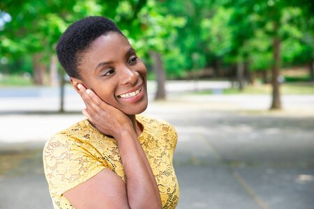 Dreamy African woman contemplating nature around. Happy attractive woman with short hair touching neck with hand. Fantasy concept Foto de archivo - 124922965