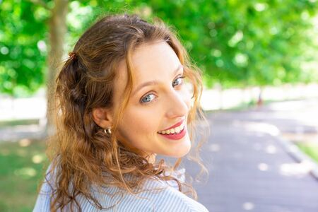 Excited young woman walking alone in park. Portrait of jolly attractive woman with wavy hair. Morning stroll concept