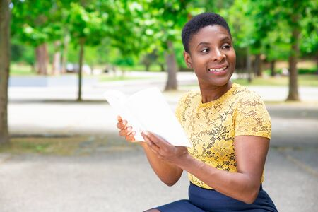 Female university student reading book on campus. Portrait of pretty Black woman spending weekend in city park. Education concept