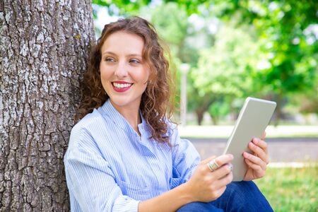 Happy beautiful woman using mobile internet on tablet. Positive pretty girl sitting by tree in summer park. Modern device concept