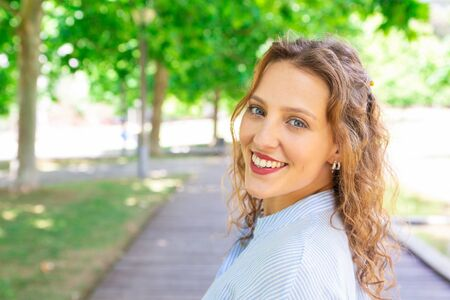 Happy wavy-haired girl smiling at camera outdoors. Portrait of cheerful young woman with earrings walking along park pathway. Summer concept