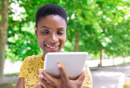 Jolly black woman laughing while using tablet outdoors. Happy pretty lady with short hair using mobile internet on gadget. Leisure in park concept