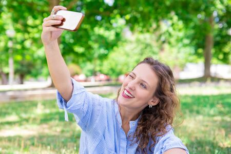 Jolly charming lady winking while taking selfie in park. Happy young woman with wavy hair resting alone outdoors. Social media concept