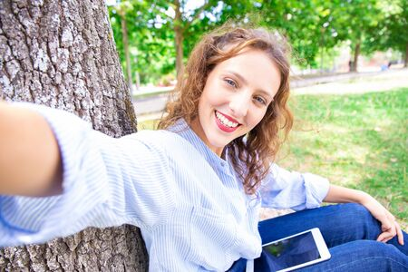 Jolly student girl taking selfie in park. Happy attractive young woman sitting on grass and using tablet. Self-portrait concept Stock Photo