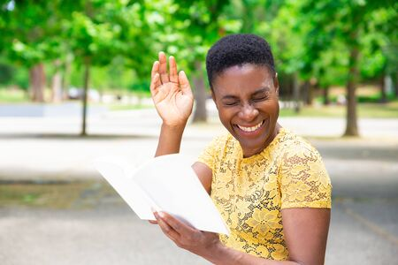 Laughing African-American woman reading joke in book. Happy beautiful woman spending time in park with book of funny stories. Literature concept Stockfoto