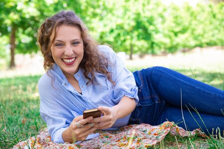 Laughing woman texting sms on phone. Positive young lady with wavy hair lying on ground and using smartphone. Online chatting concept