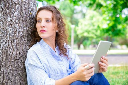 Pensive lady journalist thinking about article in park. Serious young woman with curly hair finding inspiration while sitting on grass outdoors. Technology concept Stock Photo