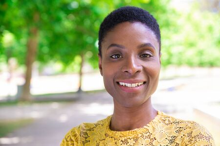 Portrait of attractive African-American lady with short hair in park. Smiling young woman in yellow lace shirt walking in city park. Confidence concept Stockfoto