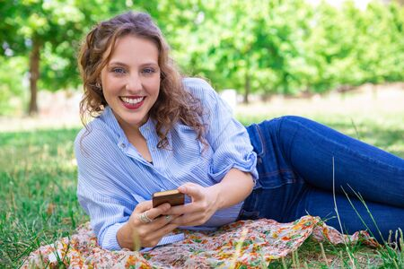 Portrait of smiling pretty girl using mobile internet on smartphone. Happy young woman lying on grass in park. Technology concept