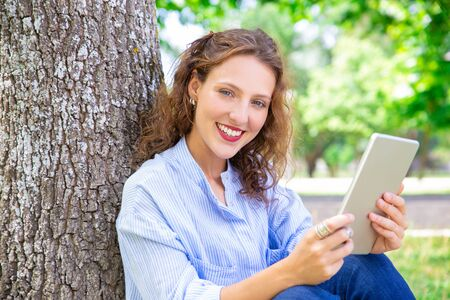 Portrait of young woman surfing net on tablet. Happy wavy-haired girl with bright lips sitting on grass in park. Modern technology concept Stock Photo