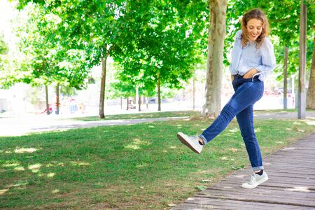 Positive woman ambling in park. Cheerful curly-haired girl in jeans walking straight leg raise outdoors. Carefree walk concept