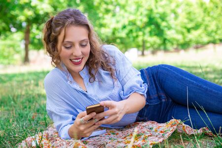 Positive young woman communicating online using smartphone. Smiling pretty lady lying on grass. Relaxing in park concept