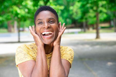 Pretty Black woman shouting from excitement. Portrait of happy beautiful young woman standing in park, covering her ears and screaming. Emotion concept Stockfoto