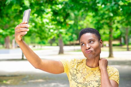 Pretty woman making duck lips for selfie. Positive beautiful African-American young woman photographing on smartphone outdoors. Self portrait concept