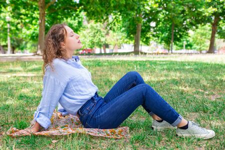 Relaxed young woman enjoying fresh air in park. Peaceful girl with wavy hair keeping eyes closed while resting alone. Serene woman concept 写真素材 - 124923015