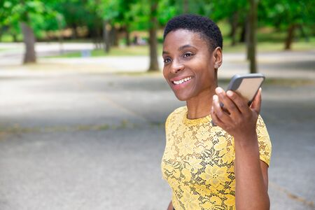 Smiling Black woman listening audio message on smartphone. Beautiful positive African-American young woman recording message for friend when walking in park. Communication concept Stockfoto