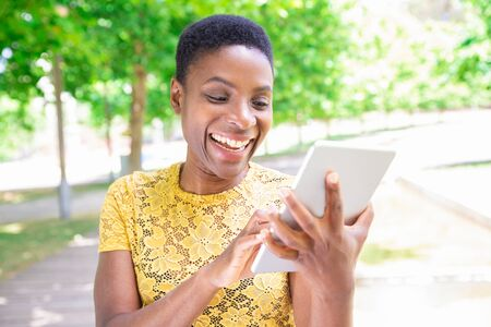 Smiling curious African lady using modern device in park. Jolly young woman with short hair surfing net on tablet. Technology concept