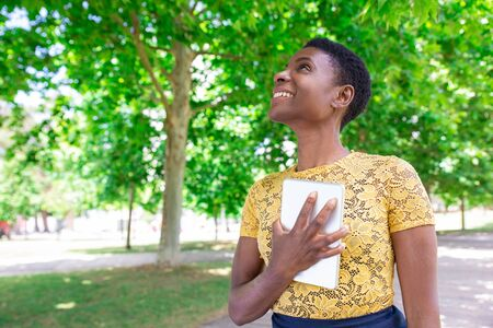 Smiling inspired black woman cuddling tablet to chest in park. Satisfied girl with short hair looking up outdoors. Aspirations concept