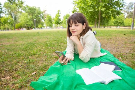 Happy content girl watching videos on smartphone while relaxing in park. Young woman lying on blanket outdoors and using mobile phone. Wi-Fi outside concept