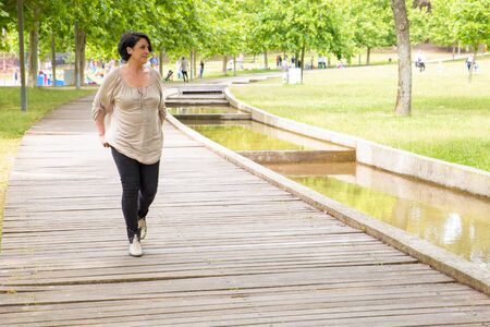 Peaceful serene woman walking outdoors. Middle aged Caucasian lady going down walkway in park and looking around. Walk in park concept