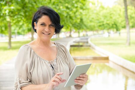 Smiling confident woman using tablet in park. Middle aged Caucasian lady standing on walkway outdoors, holding digital device and smiling at camera. Wi-Fi outdoors concept