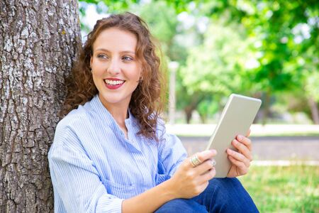 Excited pretty woman enjoying mobile app on tablet. Happy beautiful girl using gadget while resting in park. Internet concept