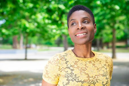 Portrait of beautiful pensive adult woman. Smiling pensive attractive Black woman standing in park. Weekend in park concept