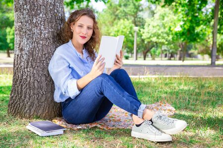 Content pretty girl reading textbook in park. Portrait of beautiful woman with curly hair sitting on blanket in park and studying information in book. Education concept