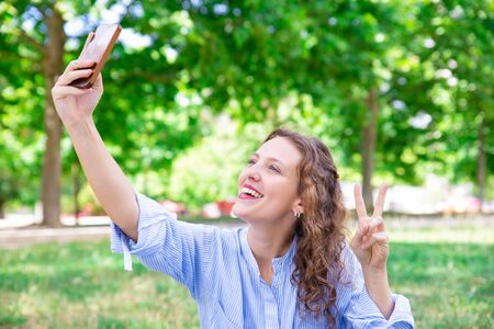 Happy young woman with wavy hair photographing herself on phone. Cheerful attractive woman in blue stripped shirt showing peace sign while posing for selfie. Social media concept