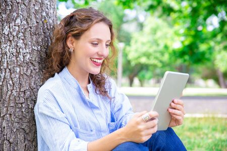 Happy young woman talking via telecommunication app on tablet. Jolly curly-haired girl chatting online in park. Video chat concept