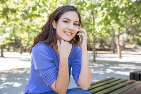 Portrait of positive modern woman calling on mobile phone outdoors. Pretty girl sitting on bench in city park. Communication concept