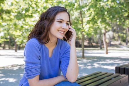 Smiling pretty woman chatting on mobile phone in park. Happy curly-haired girl sitting on bench outdoors. Communication concept