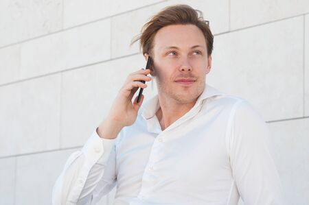 Serious business man calling on smartphone outdoors. Guy using mobile phone with building wall in background. Communication in business concept. Front view.