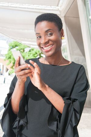 Happy delighted black woman using mobile phone app. Joyful African American lady holding smartphone and smiling at camera. Mobile online app concept
