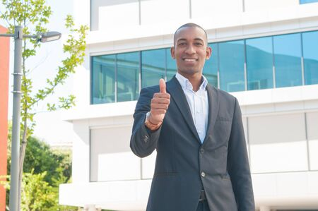 Portrait of cheerful African American man showing thumbs up. Young businessman showing satisfaction gesture. Success concept