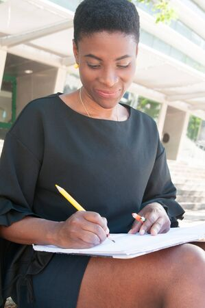 Smiling peaceful African American artist working outside. Happy black woman sitting on stairs and drawing with color pencils in album. Hobby concept