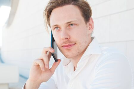 Focused business man calling on smartphone outdoors. Guy using mobile phone with building wall in background. Communication in business concept. Front view. Stock Photo