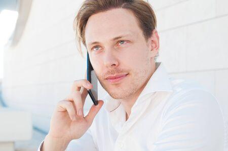 Hombre de negocios centrado llamando al teléfono inteligente al aire libre. Guy mediante teléfono móvil con muro de construcción en segundo plano. Comunicación en concepto de negocio. Vista frontal. Foto de archivo