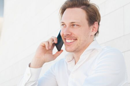 Happy business man talking on smartphone outdoors. Guy using mobile phone with building wall in background. Communication in business concept. Front view. Imagens
