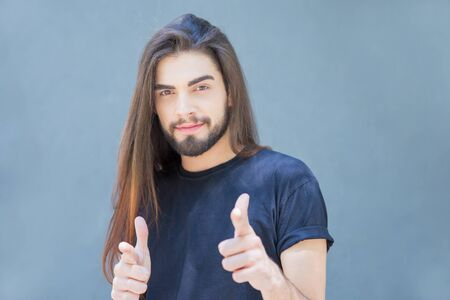 Confident smiling Latin young man pointing with finger guns. Positive attractive guy with long beautiful hair choosing you. Flirting concept