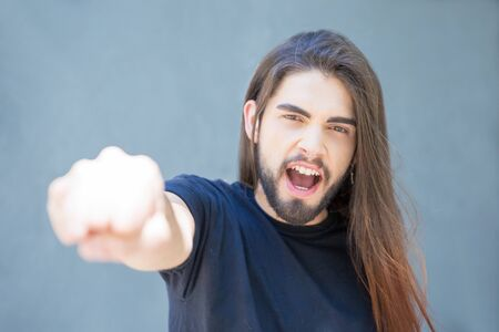 Excited shouting young man gesturing with fist clench. Rock band played with long hair doing fist bump. Greeting concept
