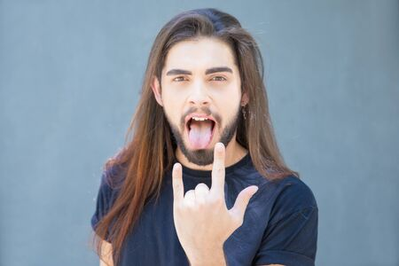 Face of attractive young man looking at camera and making rock and roll gesture. Cheerful guy sticking out tongue when showing devil horns gesture. Singer concept