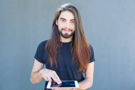 Smiling young man using tablet and looking at camera. Closeup shot of handsome stylish brunet holding modern tablet. Technology concept