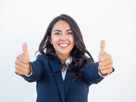 Smiling successful business leader expressing support. Happy beautiful young Latin woman in office suit showing thumbs up with both hands. Like gesture concept