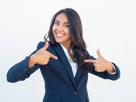 Happy joyful businesswoman pointing index fingers at herself. Cheerful delighted young Latin woman in formal suit proud of herself. Self pride concept