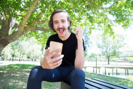 Successful young guy with smartphone looking at camera. Stylish guy with mustache holding raised fist. Technology concept