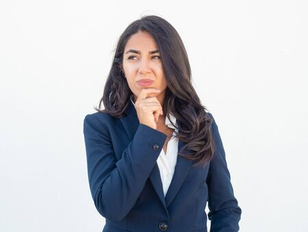 Irritated pensive businesswoman thinking over mistakes and failures. Displeased young Latin woman in office suit touching chin and looking away. Unpleasant thoughts concept